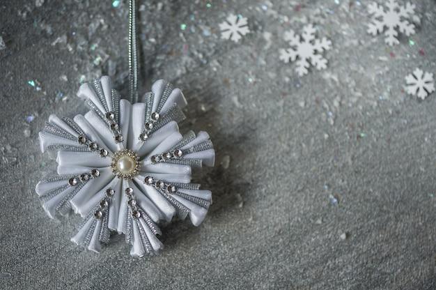 Copos de nieve decorativos de plata sobre un fondo plateado con nieve