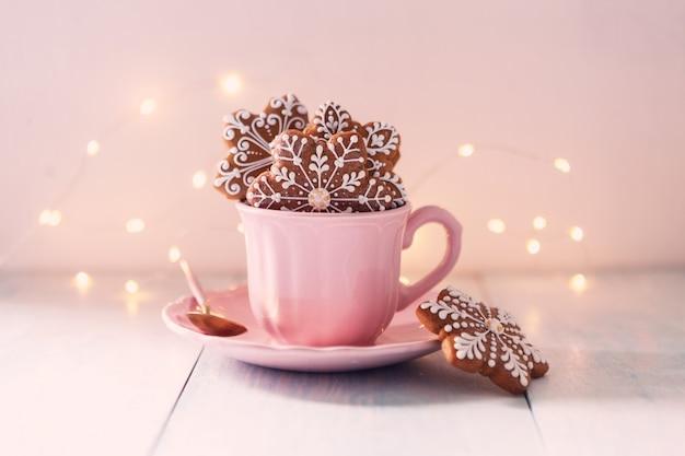 Los copos de nieve en forma de galletas de jengibre de navidad en una taza de té rosa