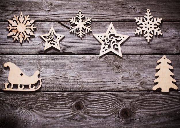 Copos de nieve de madera y estrellas sobre fondo oscuro antiguo