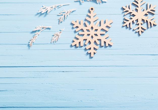 Copos de nieve de madera sobre fondo azul.
