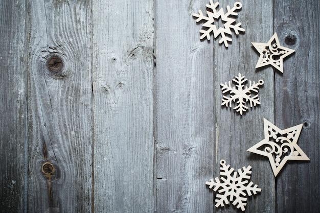 Copos de nieve de madera y srars sobre fondo oscuro antiguo