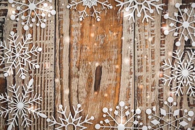 Copos de nieve de papel en el fondo de madera