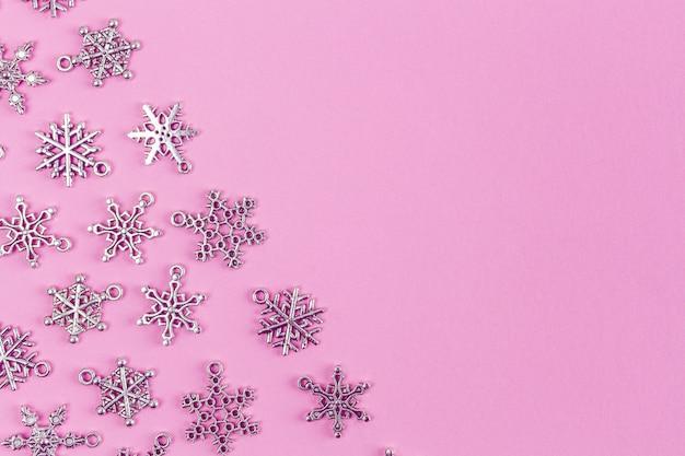 Copos de nieve de plata sobre fondo rosa con espacio de copia - tema de vacaciones
