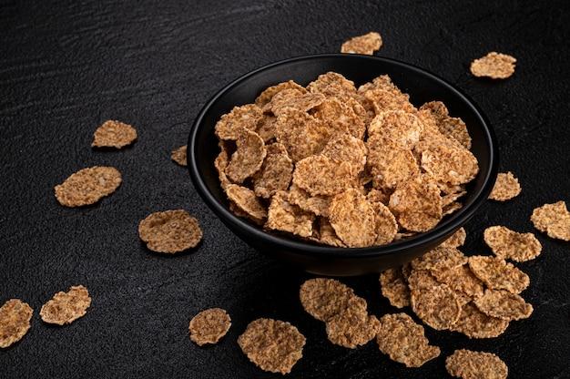 Copos de salvado en un tazón en negro con espacio de copia, cereal de desayuno saludable