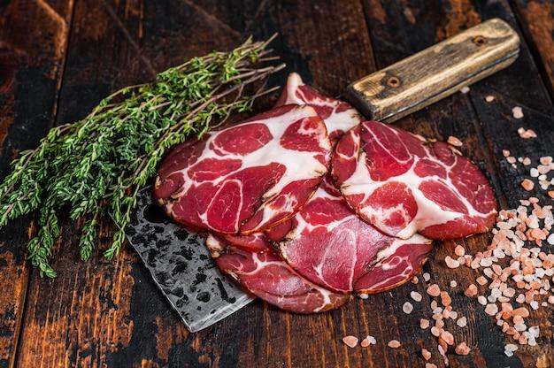 Coppa, capocollo, capicollo jamón curado en cuchillo de carnicero. fondo de madera oscura. vista superior.
