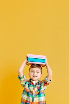 Copy-space chico lindo con libros sobre su cabeza