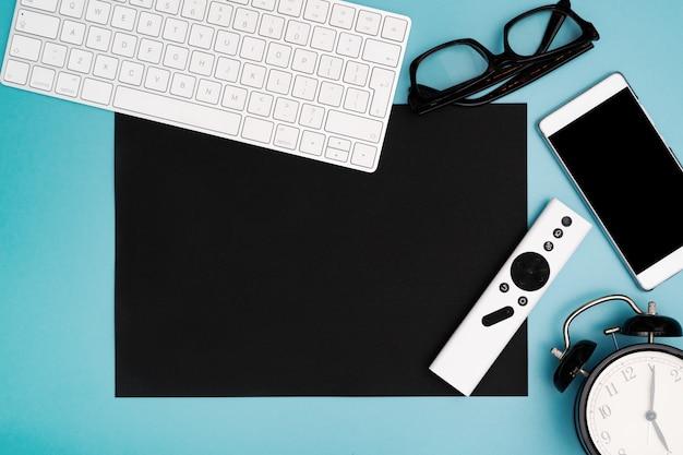Copyspace de papel negro con teclado de computadora, gafas, teléfono inteligente y reloj. topview, copia espacio