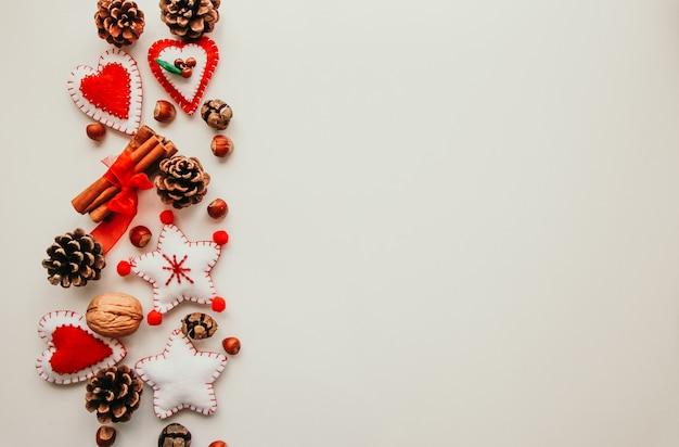 Copyspace plano de juguetes de fieltro suave como estrellas, corazones y piñas en el fondo blanco.