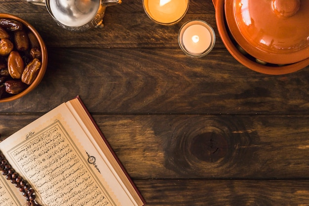 Corán abierto cerca de fechas y velas en llamas
