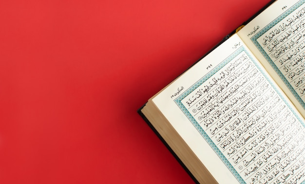 Corán abierto en un espacio llano de borgoña