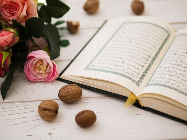 Corán abierto junto a rosas rosadas.