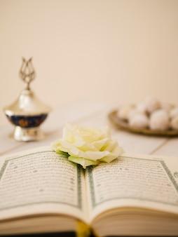 Corán abierto con rosa blanca y fondo desenfocado.