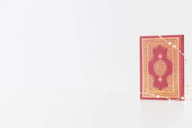 Corán envuelto en guirnaldas