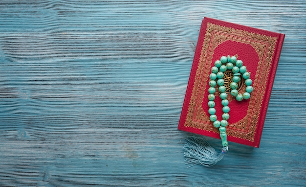Corán y rosario en mesa de madera