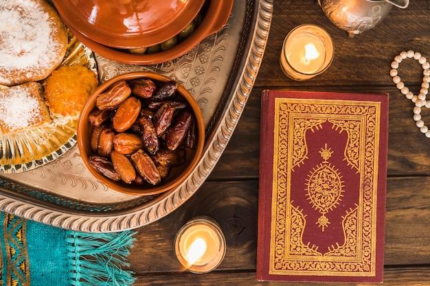 Corán y velas cerca de comida árabe