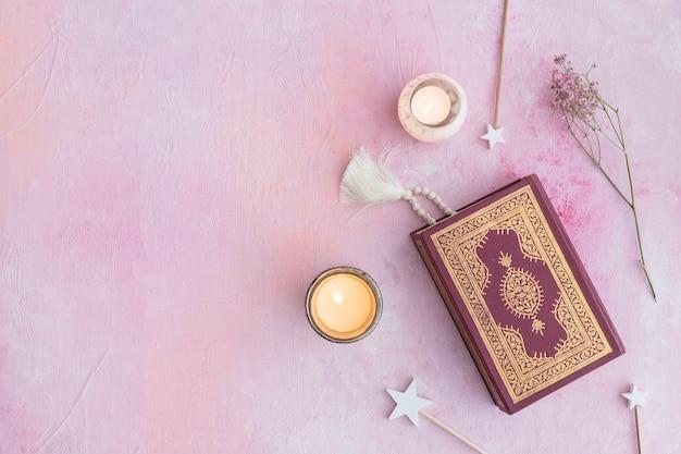 Corán y velas en rosa
