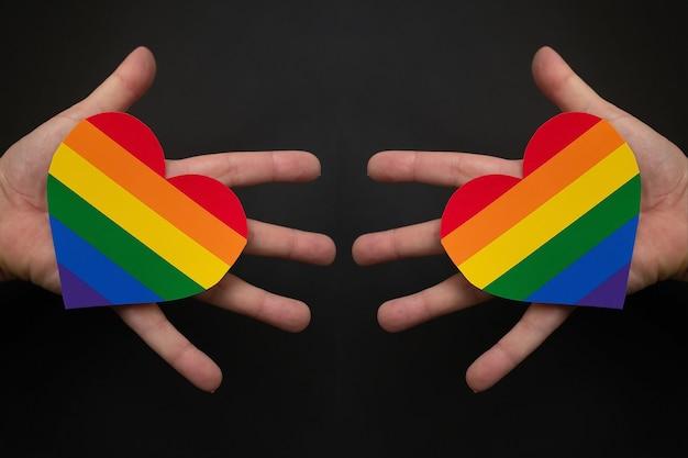 El corazón del arco iris lgbt en manos sobre un fondo negro