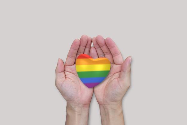 Corazón de arco iris lgbtq en manos sobre fondo blanco. libertad diversa de igualdad de amor.