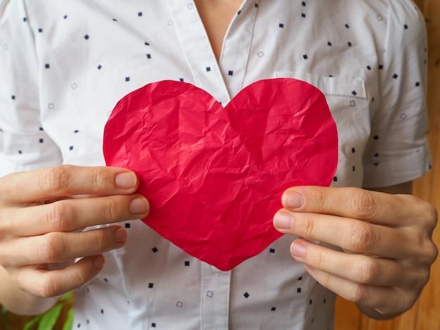 Corazón arrugado en manos femeninas. el símbolo de un corazón roto.