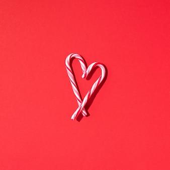 Corazón de bastón de caramelo de navidad sobre fondo rojo con espacio de copia. vista superior. amor, concepto de día de san valentín. año nuevo y tarjeta de navidad