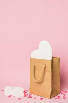 Corazón blanco en bolsa artesanal cerca de decoraciones