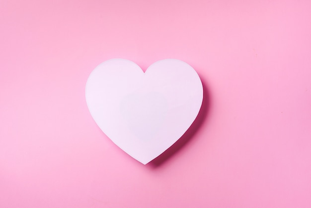 El corazón blanco cutted del papel sobre fondo en colores pastel punchy rosado con el espacio de la copia.