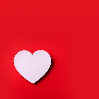 El corazón blanco cutted del papel sobre fondo rojo con el espacio de la copia. día de san valentín. amor, cita, concepto romántico.