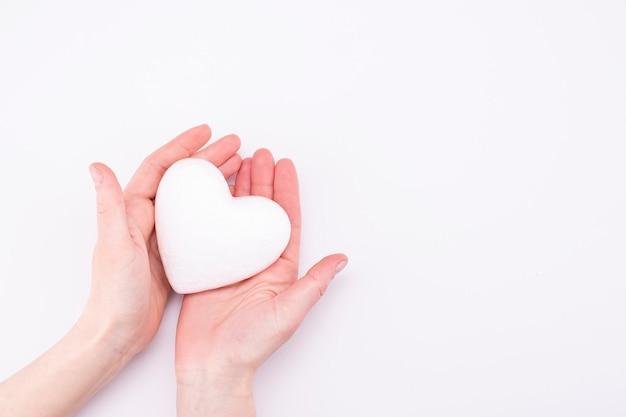 Corazón blanco en manos femeninas aisladas sobre fondo blanco con lugar para texto