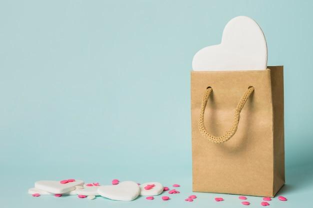 Corazón en bolsa artesanal cerca de decoraciones.