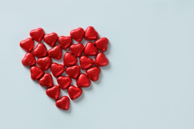 Corazón de chocolate rojo de dulces en azul. tarjeta de felicitación del día de san valentín.