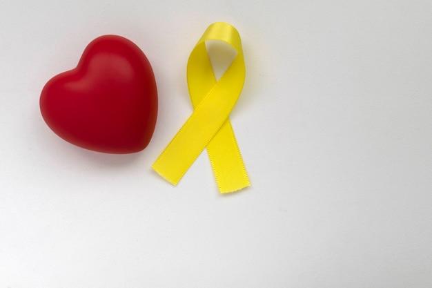 Corazón y cinta amarilla campaña de prevención del suicidio concepto amarillo de septiembre de amor y prevención