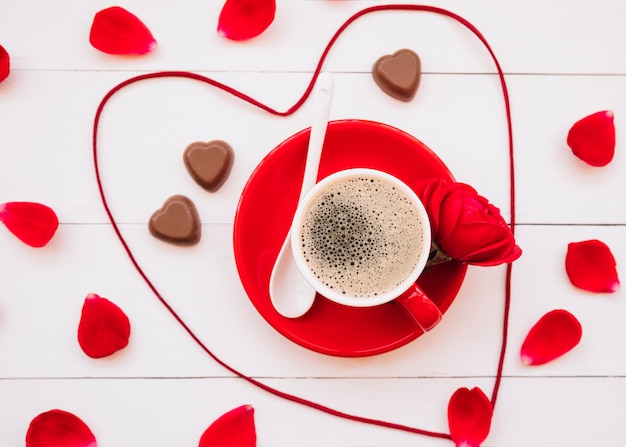 Corazón de cinta cerca de caramelos dulces de chocolate, taza de bebida en el plato y pétalos