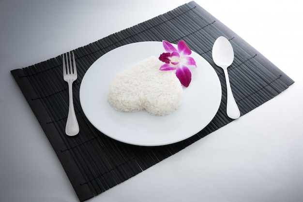 El corazón cocido del arroz forma con una cuchara y una bifurcación en el plato y la orquídea blancos