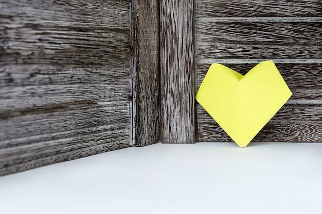 Un corazón de color amarillo de papel se encuentra en el fondo de una tabla de madera oscura
