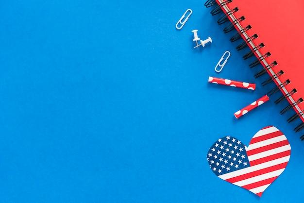 Corazón en color bandera americana y papelería en superficie azul.
