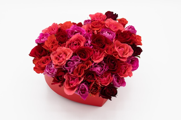 Un corazón de coloridas rosas rojas sobre fondo blanco.