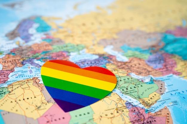 Corazón colorido del arco iris en el fondo del mapa del mundo del globo de europa, símbolo de lgbt.