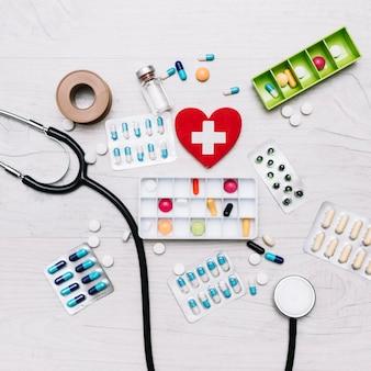 Corazón con cruz cerca de estetoscopio y medicamentos
