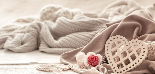 Un corazón decorativo entre acogedoras prendas de punto. concepto de vacaciones de san valentín.