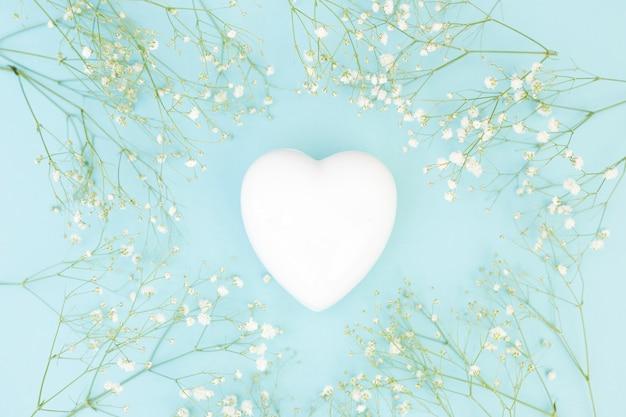 Corazón decorativo blanco entre plantas.