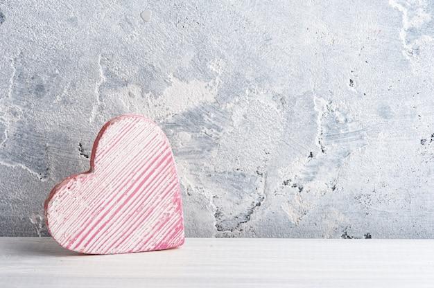 Corazón decorativo y fondo de hormigón. simulacros de boda en mesa blanca