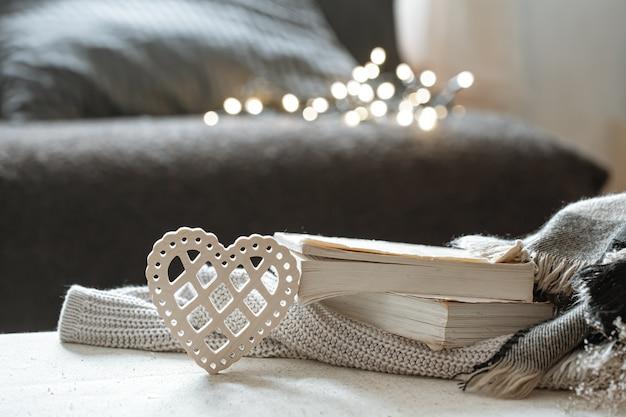 Corazón decorativo y una pila de libros con bokeh. el concepto de san valentín y la comodidad del hogar.