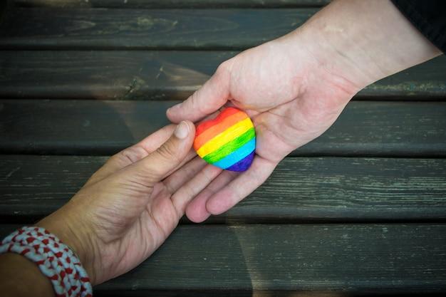 Corazón decorativo con rayas de arco iris en manos masculinas. bandera del orgullo lgbt, amor homosexual, concepto de derechos humanos.