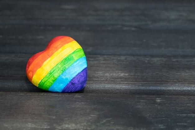 Corazón decorativo con rayas de arco iris sobre fondo de madera oscura. bandera de orgullo lgbt. derechos humanos.
