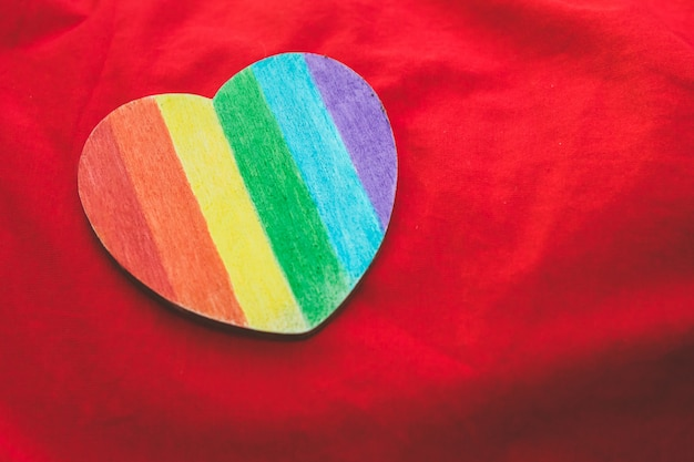 Corazón decorativo con rayas de arco iris sobre fondo rojo. bandera del orgullo lgbt, símbolo de lesbiana, gay, bisexual, transgénero.