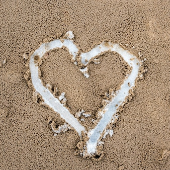 Corazón dibujado en la arena. vista superior. hay nieve debajo de la arena.