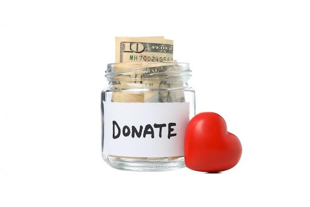Corazón y donar frasco de vidrio con dinero aislado en espacio en blanco