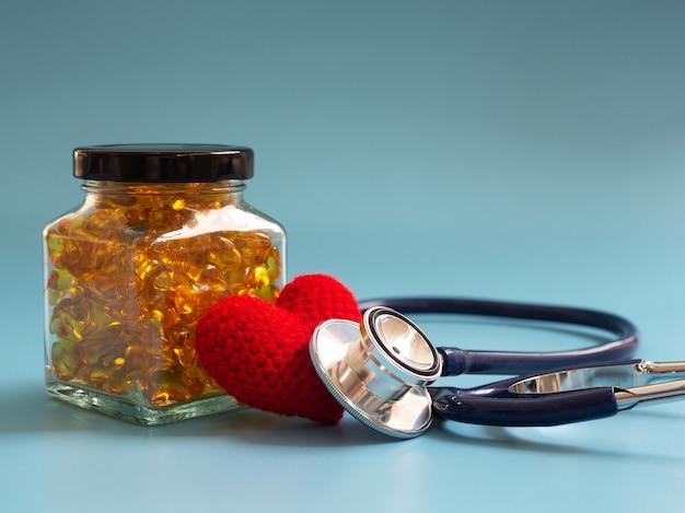 Corazón y estetoscopio rojos al lado de cápsulas del aceite de pescado en las botellas de cristal en fondo azul.