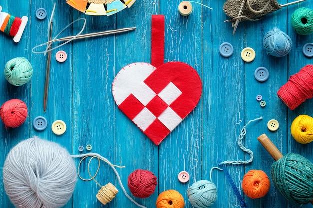 Corazón de fieltro, manojos de lana, ovillos, botones y cordón. pestillo, agujas de tejer en madera turquesa.