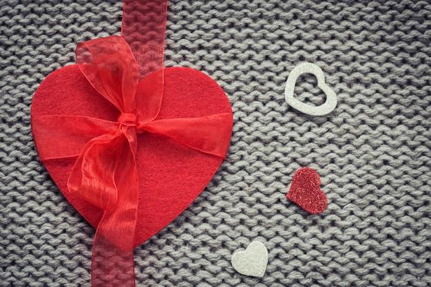Corazón de fieltro rojo y corazones decorativos coloridos